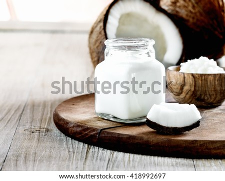 Coconut milk with coconut oil  on a wooden  board. - stock photo