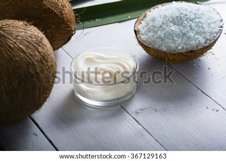 coconut moisturizer cream and bath salt , on white wood table - stock photo