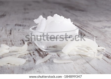 Coconut oil and coconut flakes on white textured wooden background. Healthy eating and cooking.  - stock photo