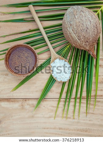 Coconut oil , coconut powder and coconut on coconut leaves set up on brown wooden background for alternative therapy. - stock photo