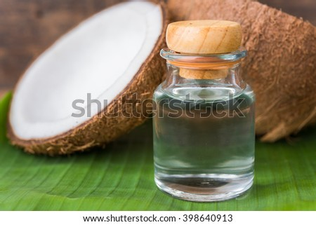 coconut oil in a bottle, background is a half of coconut on a banana leaf - stock photo