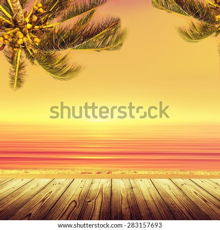 Coconut palm tree and sunset ocean landscape. Tropical paradise. Empty wooden table. - stock photo