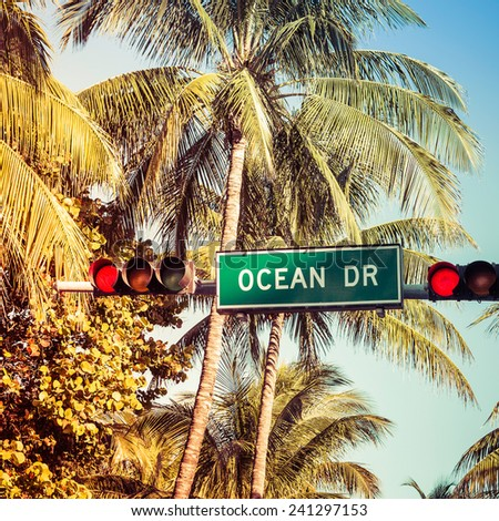 Coconut palm trees and Ocean Drive street sign in Miami Beach, Florida - stock photo