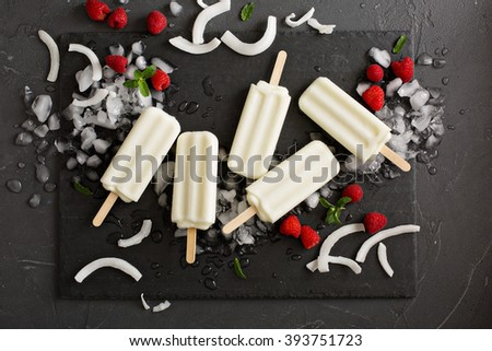 Coconut popsicles with fresh raspberries on black background - stock photo