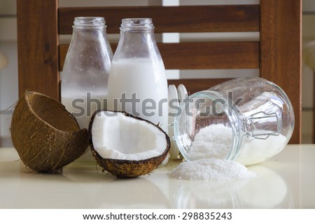 Coconut products. Cracked open coconut with meat cut in half, grounded flakes in a mason jar, flour and fresh milk in glass bottles on a table with wooden background.  - stock photo