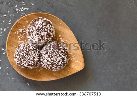 Coconut rum balls on small wooden plate, photographed overhead om slate with natural light (Selective Focus, Focus on the top of the balls) - stock photo