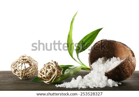 Coconut shell of sea salt with wicker balls and green petals isolated on white - stock photo