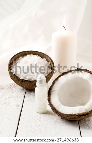 Coconut Spa composition: sea salt, coconut, coconut oil and a candle with the scent of coconut on a white background. Selective focus - stock photo