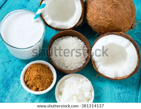 coconut sugar, milk and oil on wooden surface - stock photo