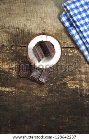 Coconut with chocolate on old wooden background - stock photo
