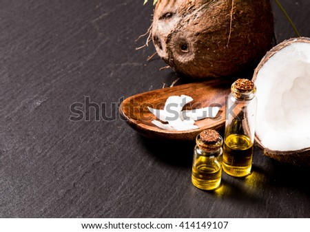 Coconut with coconut oil in jar on black background - stock photo