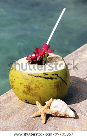 Coconut with drinking straw in summer - stock photo