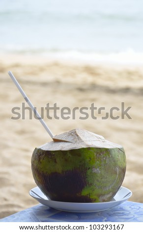 Coconut with drinking straw on a beach - stock photo