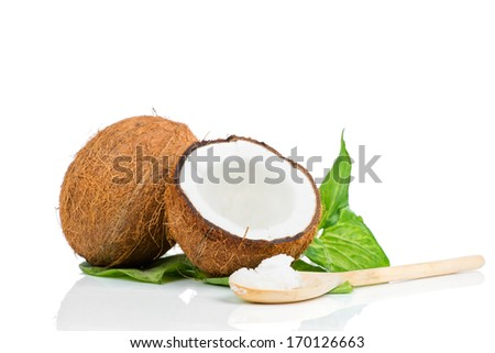 Coconut with green leaf and wooden spoon - stock photo