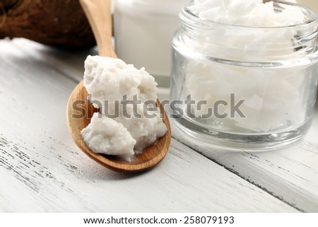 Coconut with jars of coconut oil and cosmetic cream on table close up - stock photo