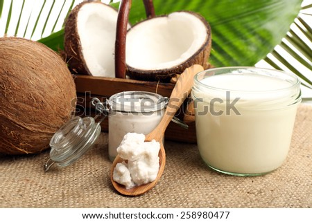 Coconut with jars of coconut oil and  milk on sackcloth on natural background - stock photo