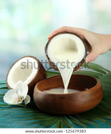 Coconut with leaves and flower, on blue wooden background - stock photo