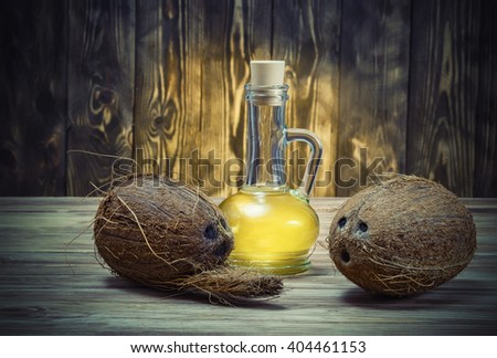 Coconuts and a bottle of coconut oil on wooden table . - stock photo