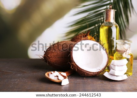 Coconuts and coconut oil on wooden table - stock photo