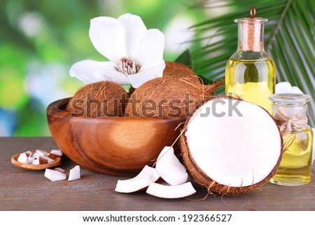 Coconuts and coconut oil on wooden table, on nature background - stock photo