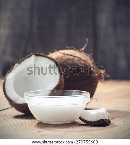 Coconuts and organic coconut oil in a glass jar  - stock photo