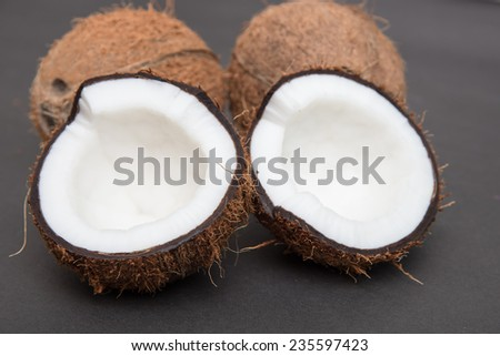 Coconuts cut in half and whole coconuts - stock photo