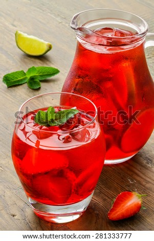 Coctail. Refreshing summer drink with Strawberry in jug and glass on rustic wooden table - stock photo