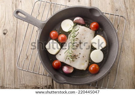 cod fillet with tomato, garlic, onion, rosemary and crushed pepper in a cast iron pan - stock photo
