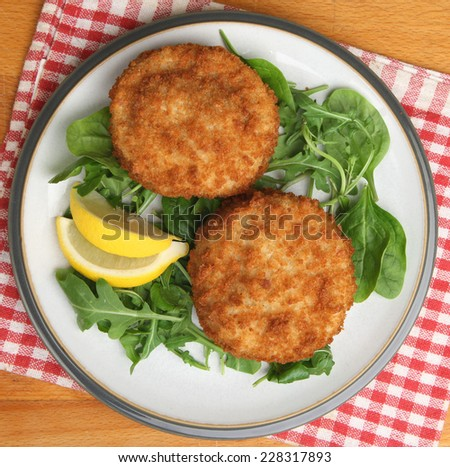 Cod fishcakes served with a rocket, spinach and watercress salad. - stock photo