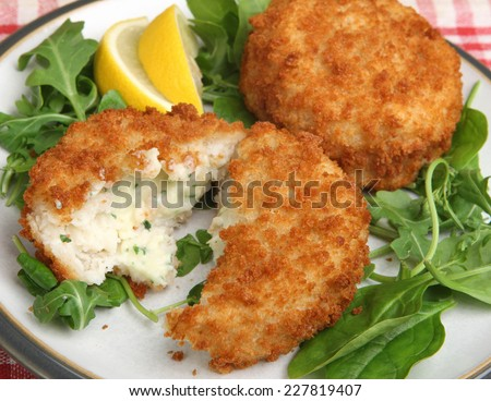 Cod fishcakes with rocket, spinach and watercress salad. - stock photo