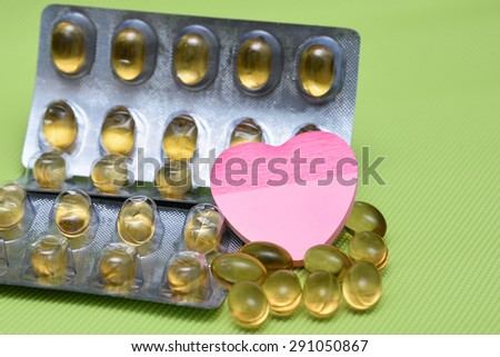 Cod liver fish oil omega 3 gel capsules isolated on green background. heart shaped paper copy space for text. metal foil blister strip packaging.nutritional supplement contains Vitamin A and Vitamin D - stock photo