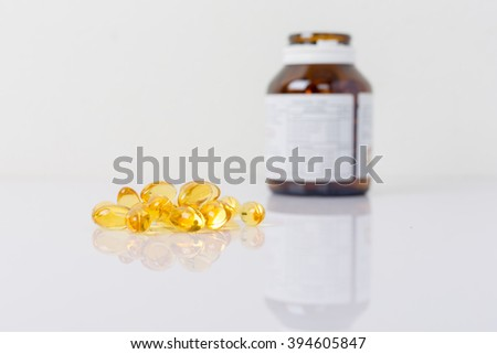 Cod liver oil capsules with a brown bottle on white. - stock photo