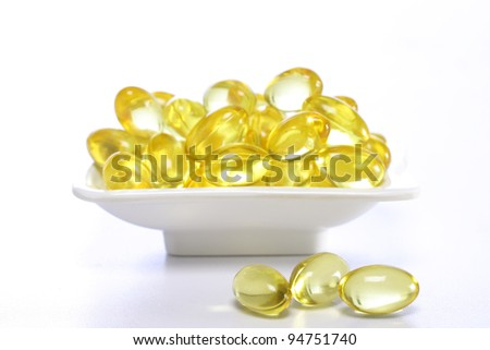 Cod liver oil pills in a white bowl - stock photo