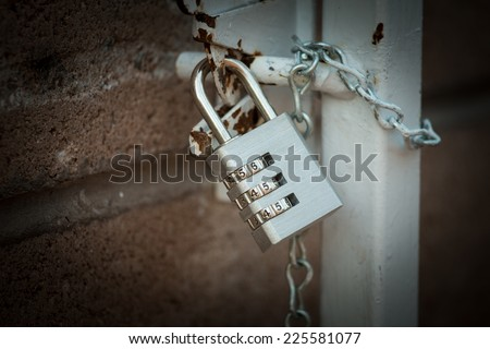 Coded lock locked on a chain - stock photo