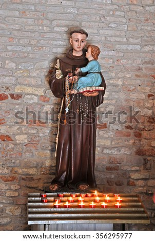CODIGORO, ITALY-MAY 10, 2015: Pomposa Abbey Saint Mary church interior monk with baby Jesus statue. The place attract thousands of people every year. - stock photo