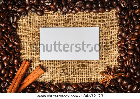 Coffe frame made of beans on burlap with star anise, cinnamon and visiting card in it - stock photo