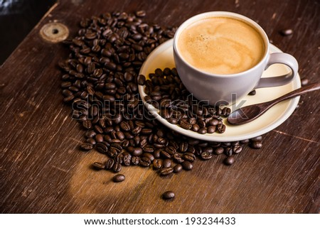 coffee americano with coffee beans on wooden table - stock photo