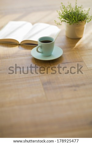 Coffee and a book and houseplant - stock photo