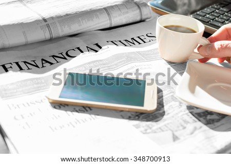 Coffee and cell phone and newspaper with inscription financial time - stock photo