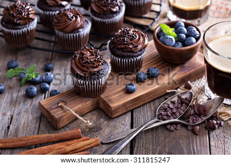 Coffee and chocolate cupcakes on wooden table  - stock photo