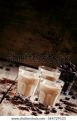 Coffee and cream liqueur, coffee beans roasted and ground coffee on the old wooden background, selective focus - stock photo