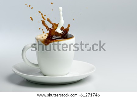 Coffee and milk splashing in white cup. Pouring milk into coffee. - stock photo