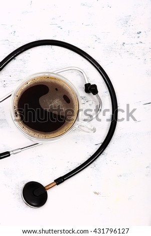 Coffee and stethoscope on white table background. - stock photo