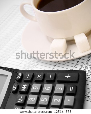 Coffee and the calculator on documents. - stock photo