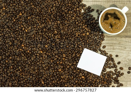 Coffee bean background with cup of fresh hot coffee and space for text on kitchen table - stock photo