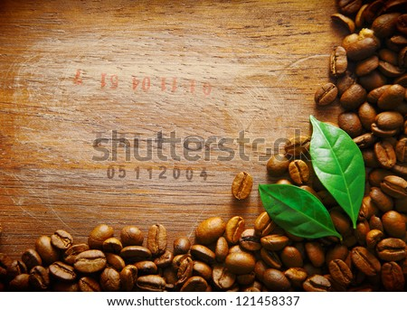 Coffee bean border on an old wood surface with stamped numbers from a shipment of coffee beans with two green leaves - stock photo
