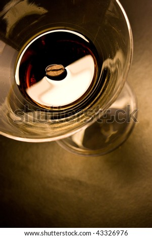 Coffee bean in a martini glass filled with coffee liquor - stock photo