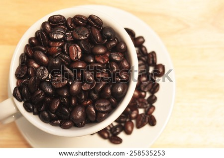 coffee bean in cup on wooden background - stock photo