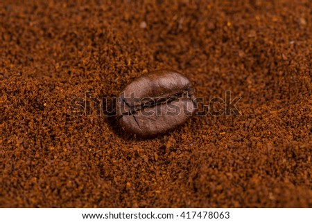 Coffee bean on heap of ground coffee close-up. - stock photo