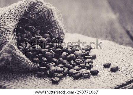 Coffee bean spill out from bag. Dramatic black and white photo. - stock photo